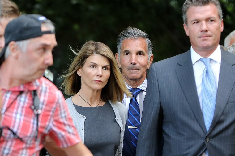 Lori Loughlin, center left, and her husband Mossimo Giannulli, center right, leave the John Joseph Moakley United States Courthouse in Boston on Aug. 27, 201