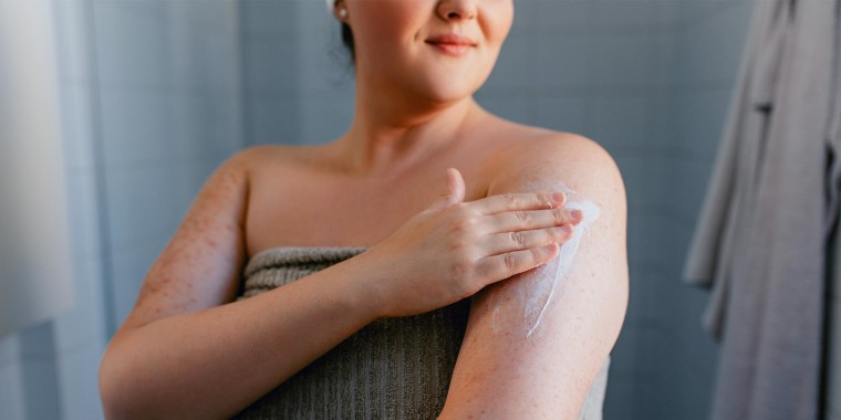 Woman in a towel, in her bathroom, rubbing lotion on her arm