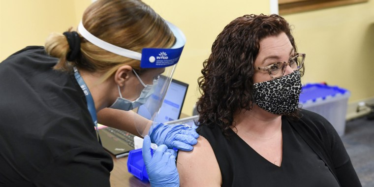 Masked woman with brown curly hair and glasses gets vaccination from health care worker