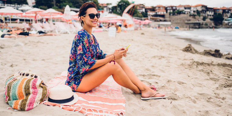Image of a Woman sitting on the beach sitting on her pink striped beach towel