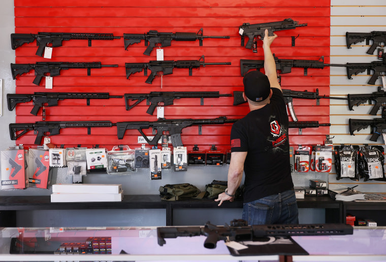 Image: Brandon Wexler helps a customer look at weapons at WEX Gunworks on March 24, 2021 in Delray Beach, Fla.