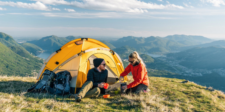 Couple sitting in front of a yellow camping tent, overlooking the mountains
