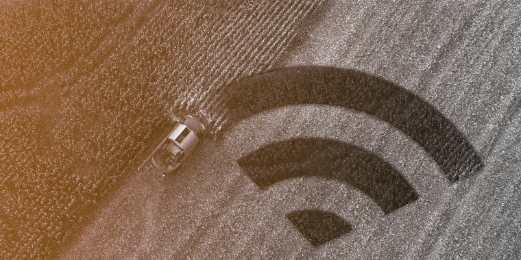 Photo illustration of harvester gathering corn crop in a field and the cultivated part of the land is in the shape of the wireless connectivity symbol.