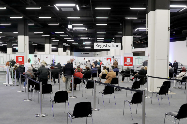 People wait at the Impfzentrum Stadt vaccination center at the Congress Center in Basel, Switzerland on March 18, 2021.