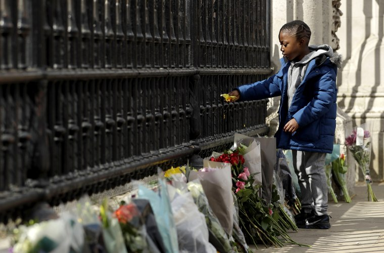 Image: A young boy places a flower on the gate at Buckingham Palace in London, after the announcement of the death of Britain's Prince Philip, April 9, 2021