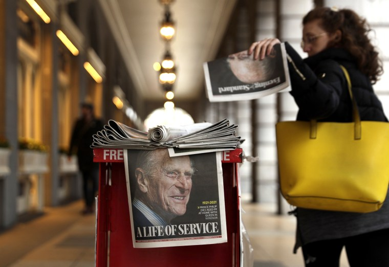 Image: A woman picks up a newspaper with a tribute to Britain's Prince Philip on the front page at Leicester Square in London on April 9, 2021.