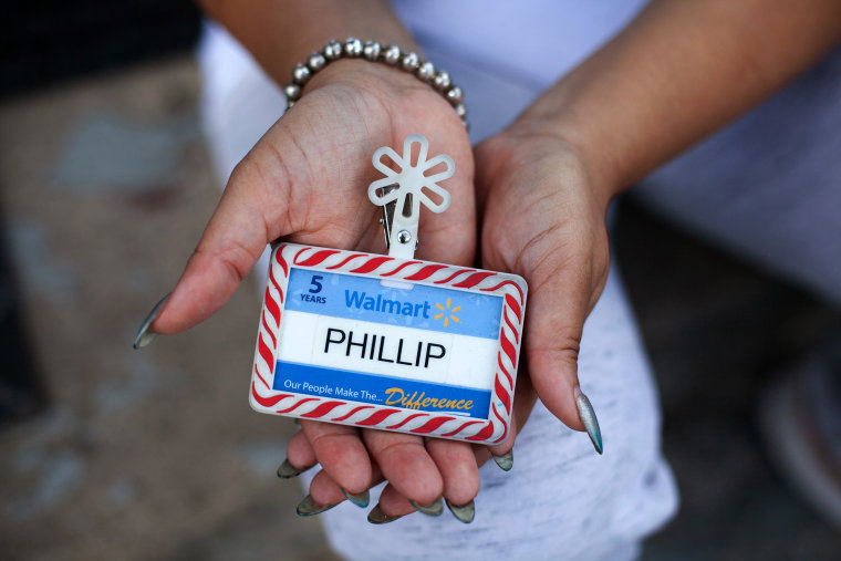 Image: Angela McMiller holds her late brother Phillip Thomas' Walmart employee badge.