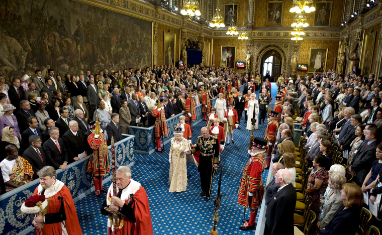 Britain's Queen Elizabeth II and Prince Philip walk through the Royal Gallery in the Palace of Westminster during the State Opening of Parliament, in London, on May 25, 2010.