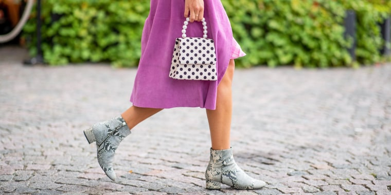Woman in a purple dress, and snakeskin booties, holding a spotted purse with pearls