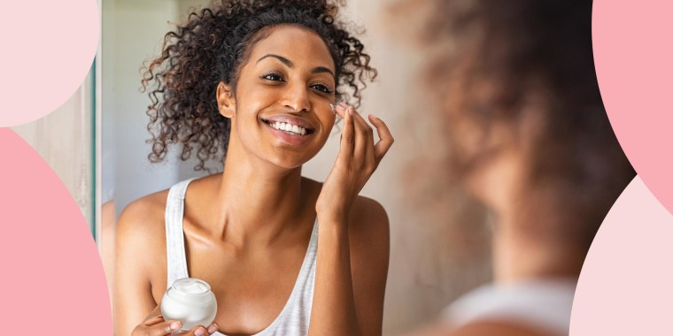 Woman putting lotion on her cheek while looking in the bathroom mirror