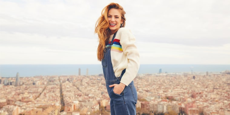 Red-head Woman wearing jean overalls with a beige sweater, outside