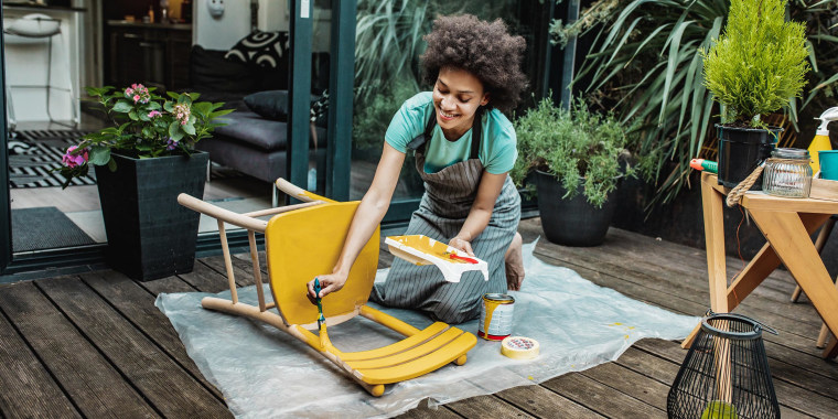 Woman paining a wooden chair yellow, outside on her patio