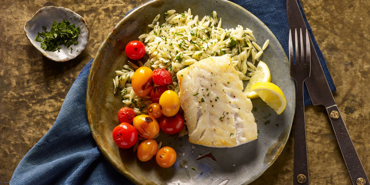 Cooked fish on a plate with tomatoes and rice
