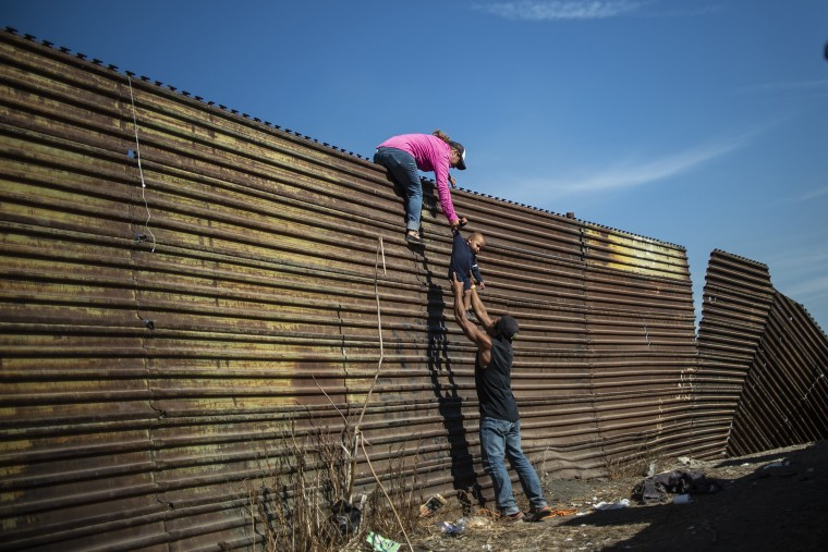 Image: A group of Central American migrants climb the border fence between Mexico and the United States, near El Chaparral border crossing, in Tijuana, Baja California State, Mexico, on Nov. 25, 2018.