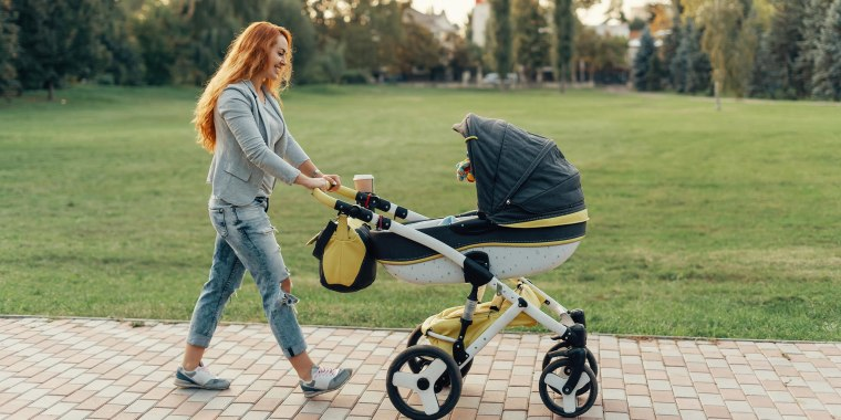 Woman pushing a yellow and black stroller through a park.  Shop the best strollers of 2021 including baby strollers, double strollers, car strollers and umbrella strollers from Chicco, Nuna, Doona, UPPAbaby and more.