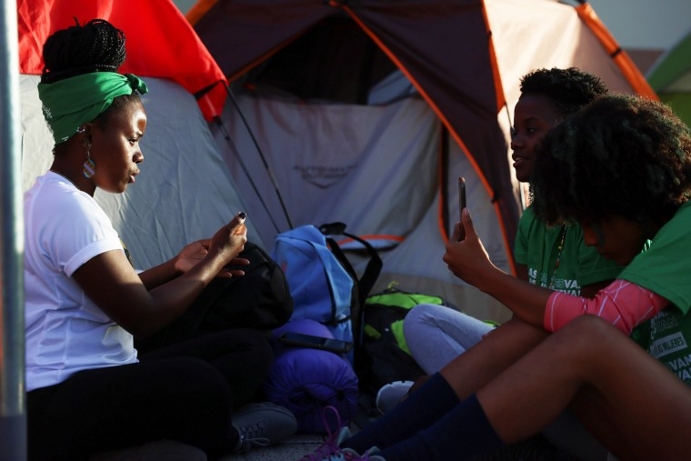 Abortion rights activists sit outside tents set up in front of the National Palace during a protest to pressure parliament over a proposed reform to the penal code that could end the total ban on abortion in Santo Domingo, Dominican Republic, on March 18,