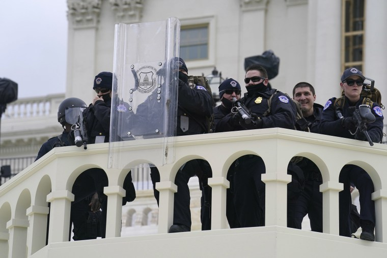 Image: U.S. Capitol Police officer stand as violent rioters storm the Capitol, in Washington