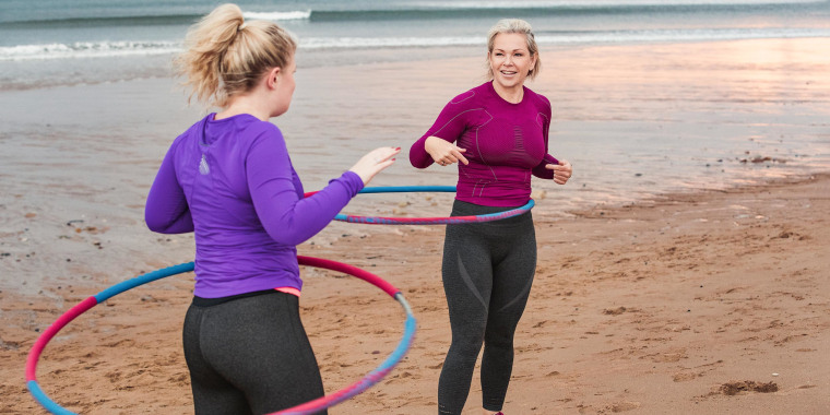 Two Woman on the beach, wearing workout clothes, using pink and blue weighted hula hoops to work out. Weighted hula hoops can be a great workout when used properly. Learn how to workout with an exercise hula hoop and shop the best weighted hula hoops.
