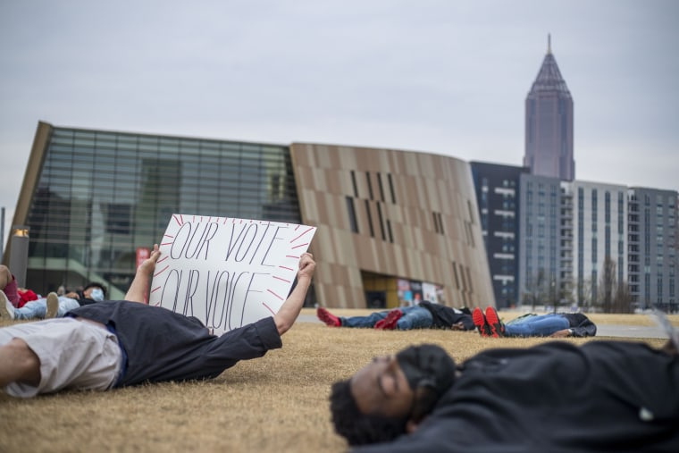 """Demonstrators participate in a \""""die-in\"""" peaceful protest outside of the World of Coca-Cola in downtown Atlanta on March 15, 2021."""