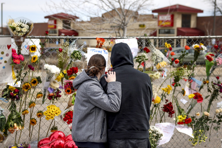 Image: People who knew shooting victim Neven Stanisic comfort each other at a makeshift memorial outside a King Soopers grocery store on March 25, 2021 in Boulder, Colo.