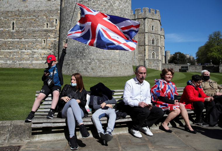 Image: People sit outside Windsor Castle on the day of the funeral of Britain's Prince Philip, husband of Queen Elizabeth, who died at the age of 99, in Windsor, near London