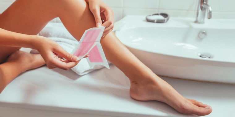 Woman using a pink wax strip on her legs, sitting on the bathroom counter