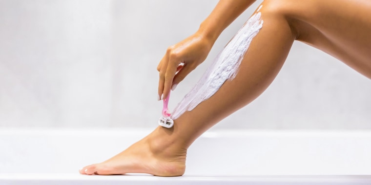 Woman sitting on rim of her tub shaving her leg with a pink razor
