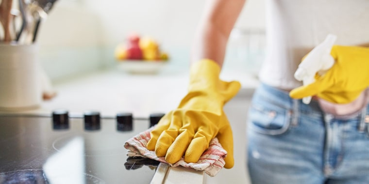 Woman wiping her counters down, wearing yellow cleaning gloves