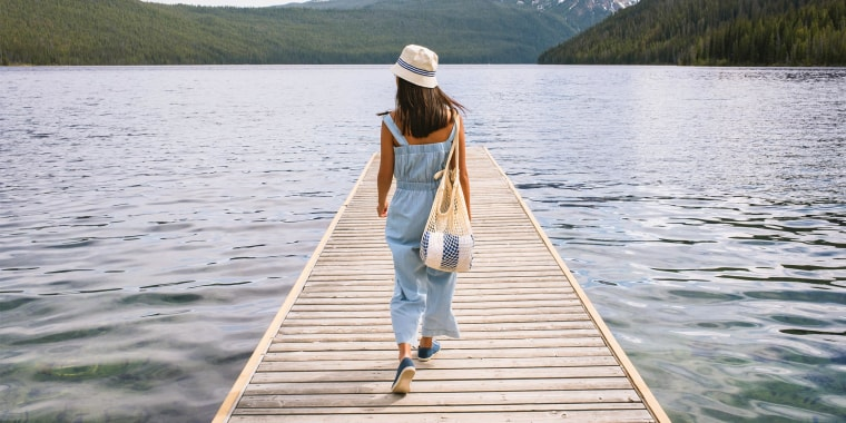 Young woman walking on dock at mountain lake wearing a jumpsuit