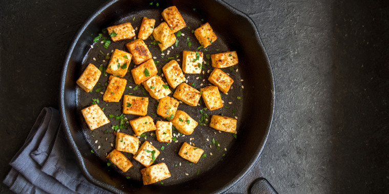 Fried tofu with sesame seeds and spices on cast iron pan, copy space. Healthy ingredient for cooking vegan vegetarian diet food. Roasted tofu over bla