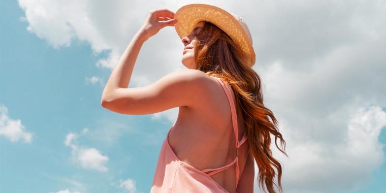 Portrait of redheaded woman enjoying sunlight, wearing a pink dress and a sun hat