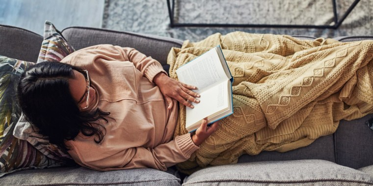 Woman laying on her couch reading a book, wrapped in a yellow throw blanket