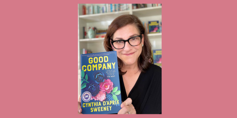 "D'Aprix Sweeney holds a copy of her second novel, titled ""Good Company."""