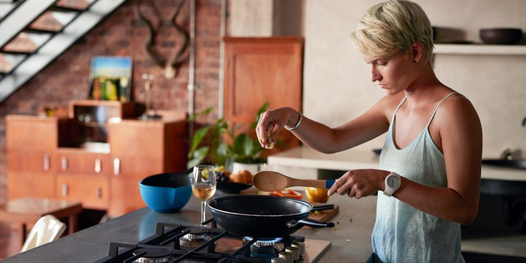 Woman standing in her kitchen cooking with a pan. Shop the best Mother's Day gifts for foodie moms and moms who love cooking. The best Mother's Day kitchen gifts include cutting boards, pans and more.