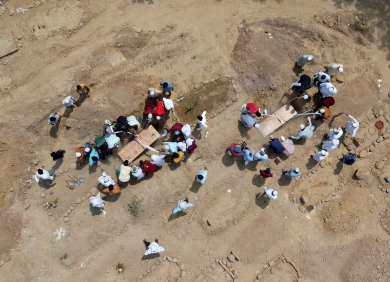 Image: People bury the bodies of victims who died due to Covid-19, at a graveyard in New Delhi, India