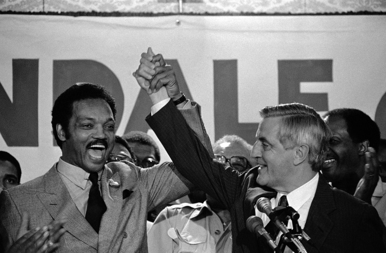 Image: The Rev. Jesse Jackson, left, and Democratic presidential nominee Walter Mondale lift their arms in St. Paul, Minnesota on Aug. 29, 1984, after Mondale met with Black leaders.