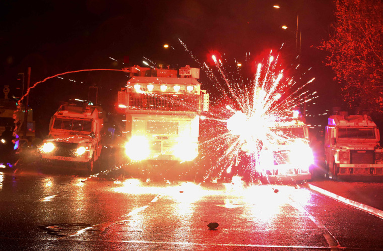 Image: Fireworks explode at police vehicles after being fired at police officers with a water cannon during clashes with nationalist youths in the Springfield Road area of Belfast