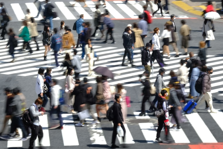 Image: Pedestrians wearing face masks walk over the landmark Shibuya Crossing in the area's shopping and entertainment district in Tokyo