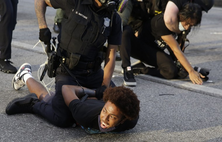 Image: Protestors being detained by police officers.