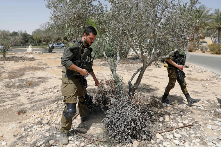 Image: Israeli soldiers search for debris after a missile launched from Syria landed in the vicinity of the Dimona nuclear site in Israel's southern Negev desert