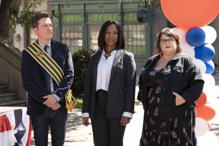 "Ed Helms as Nathan Rutherford, Dana L. Wilson as Mayor Deirdre, Jana Schmieding as Reagan Wells in ""Rutherford Falls\"" on Peacock."
