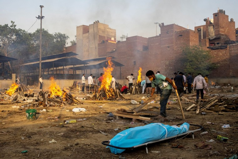 Image: A man prepares a funeral pyre to cremate the body of a person, who died due to the coronavirus disease (COVID-19), at a crematorium ground in New Delhi