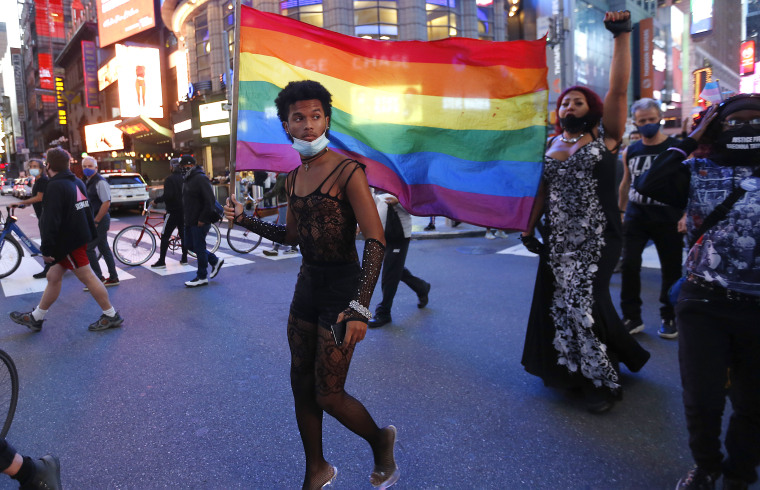 A protester holds a rainbow flag in support of transgender rights