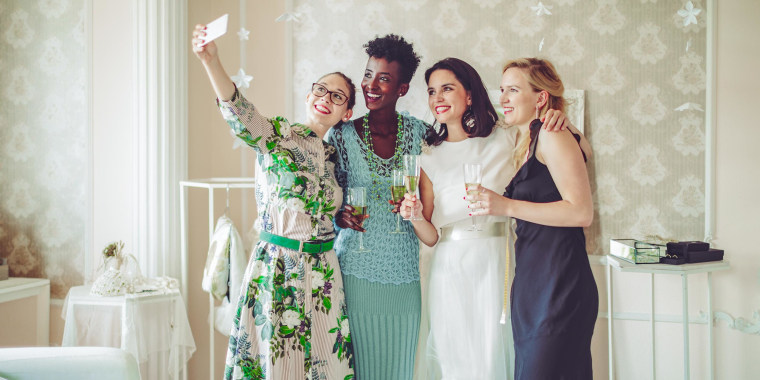 Group of friends wearing different dresses, taking a selfie with the bride