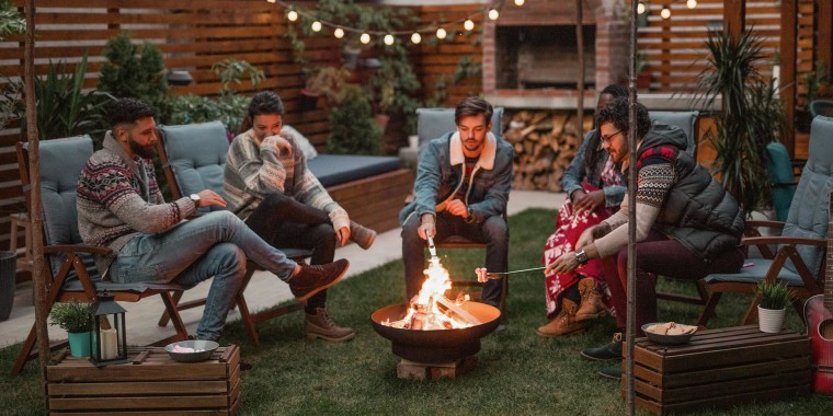 Group of friends in a backyard, roasting marshmallows over a fire pit