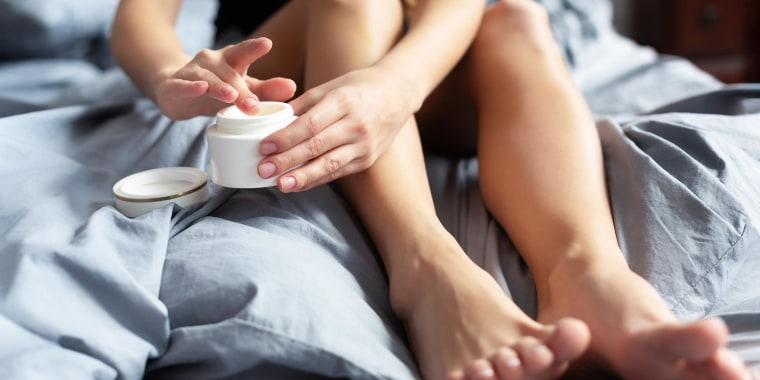 Woman taking lotion with her finger, while sitting on her bed