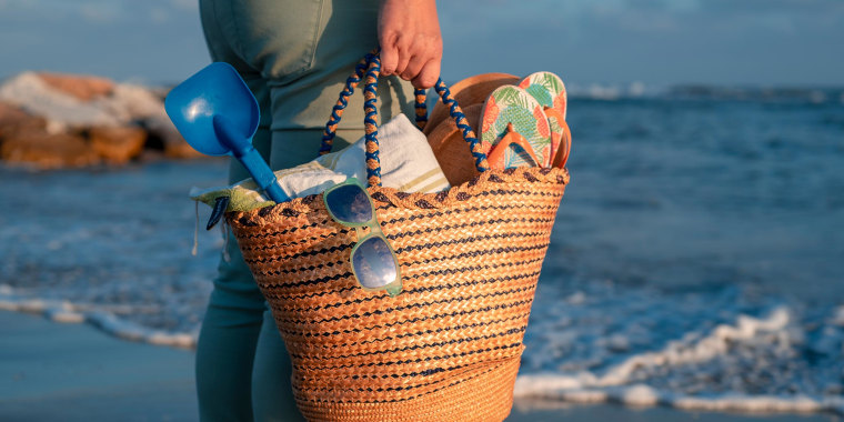 Woman holding a bag filled with glasses, towel, shovel, flip-flops, book at the beach at sunset