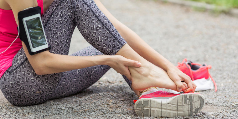 Woman sitting on the ground rubbing her foot out of her pink sneaker