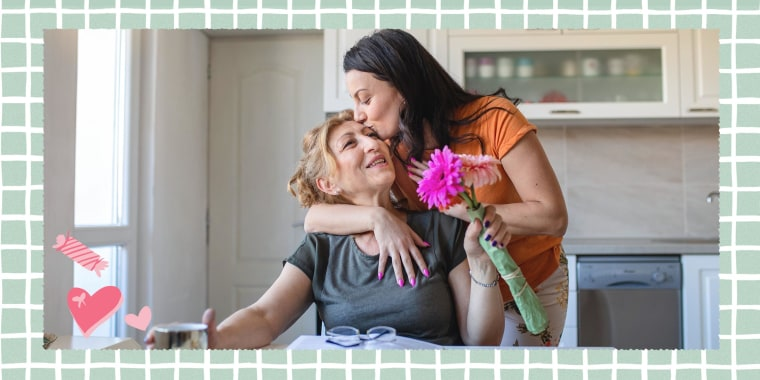 Daughter surprising her mother with flowers for mothers day