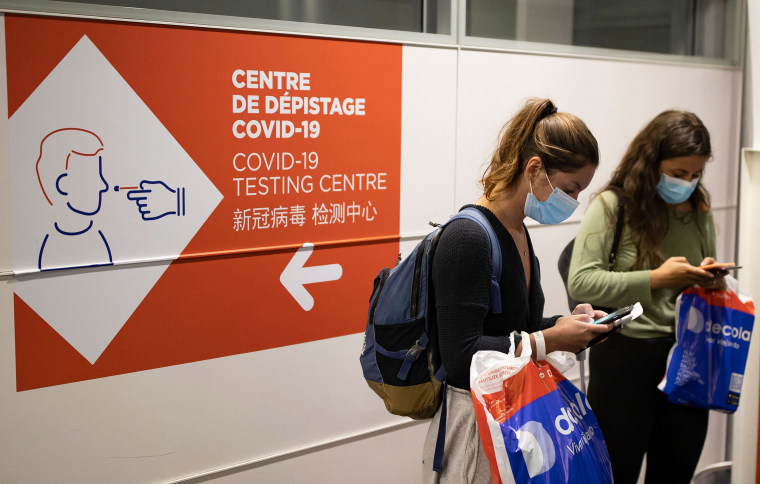 Image: Passengers check their telephones next to a sign indicating the way to a sanitary control point for passengers arriving from countries listed as Covid-19 red zones, in Roissy Charles de Gaulle airport in Roissy, near Paris